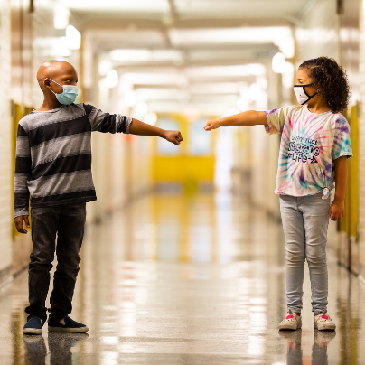 two students reaching out in school hallway