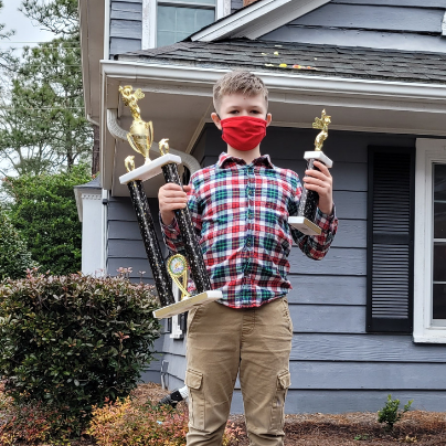 Spelling Bee Winner Zachary Thurnher holding trophies in front yard