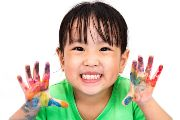 Happy student  with finger paint on her hands